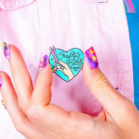 "Punky Pins Crafty Bitch Enamel Pin, heart shaped pin with a hand and a pair of scissors, with the words ""craft bitch"""