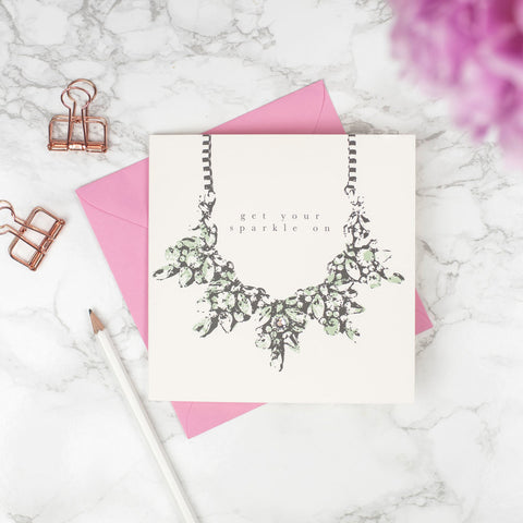 "Studio Seed Get Your Sparkle On Greeting Card This beautiful crystal necklace designed card , with the words ""Get your sparkle on"", hand finished with a Swarovski crystal for a touch of lux is perfect to let your your loved one know how special they are. This is not just a card but a keepsake your loved ones can treasure forever."
