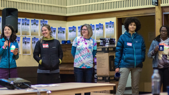 five women with trail name tags standing. One holds a microphone.