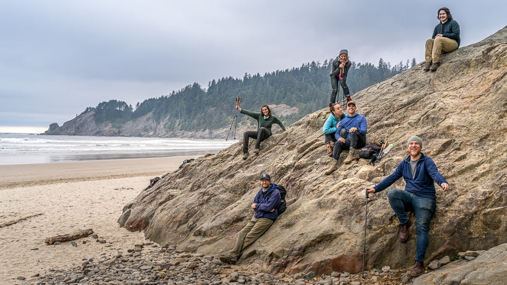 Staff of Cnoc Outdoors pose on a large rock at the beach.