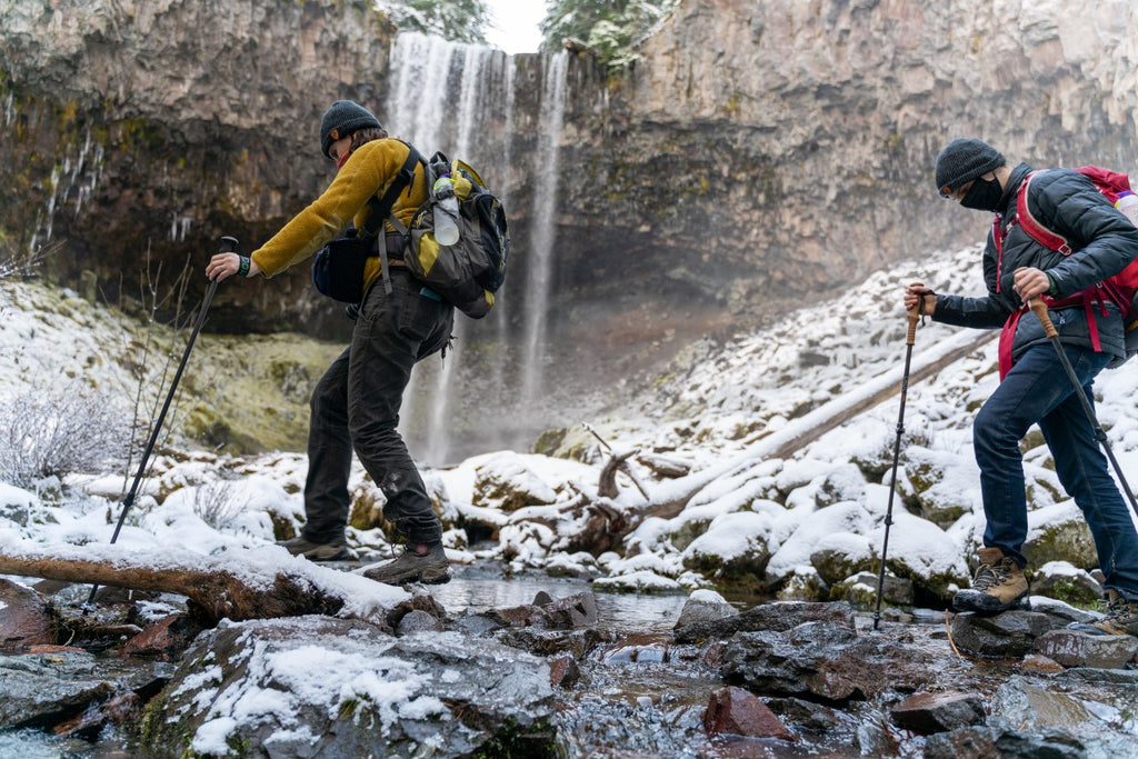 Two hikers with trekking poles and packs hike on snowy and icy terrain in front of a frozen waterfall landscape. hiking, kids, backpacking, camping, outdoors, teens, family