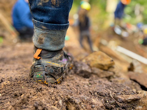 A close up shot of an extremely muddy section of hiking trail, with a person standing in jeans and boots, with yellow Mudpons Traction Devices helping their grip on the trail.  In the background, out of focus trailworkers volunteer to rebuild trail.  trailkeepers, oregon, northwest, pacific northwest, oregon coast, oregon coast trail, trail building, trail work, volunteer, trailkeepers of oregon, mudpons, traction, hiking