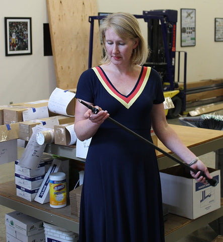 woman (Amelia) holds a trekking pole in a warehouse
