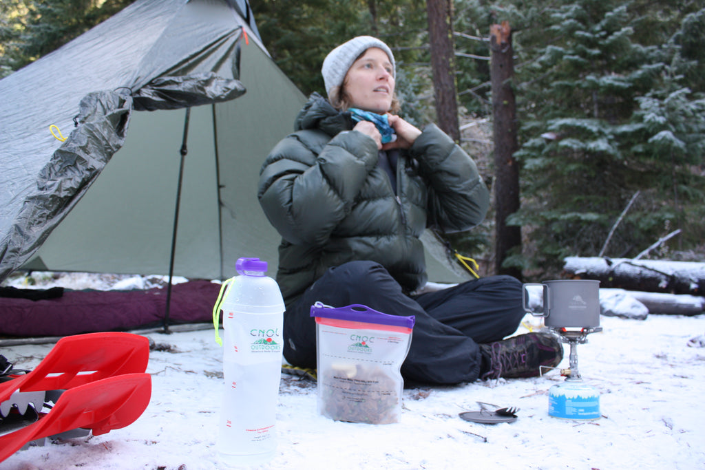 woman solo winter camping with cnoc outdoors gear