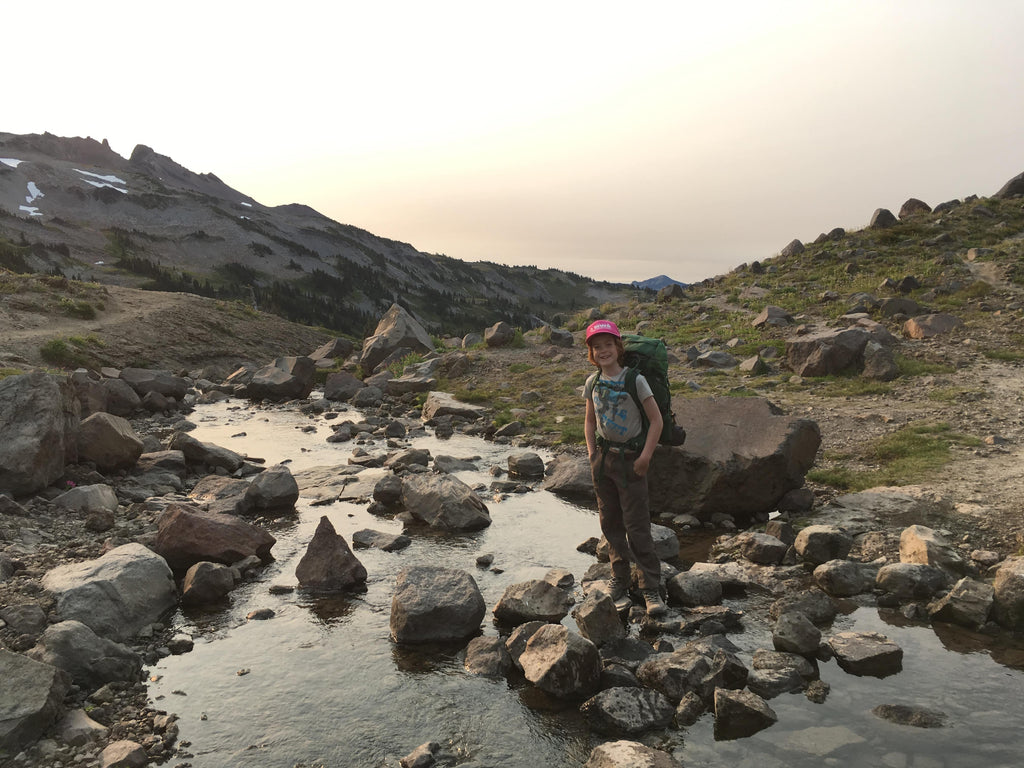 An elementary-aged child wearing a pink ball cap and a backpacking pack stands at the edge of a rocky mountain creek, with tall peaks and snow behind them. hiking, kids, backpacking, camping, outdoors, family