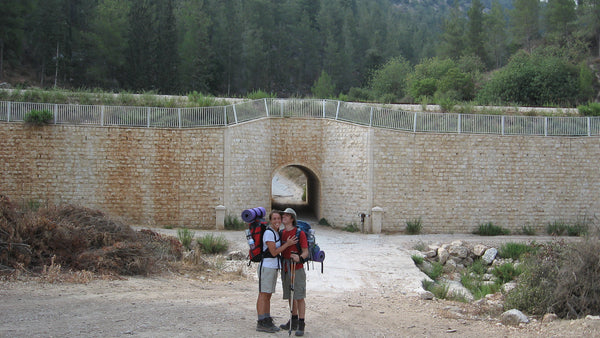 young man and woman with backpacking packs on stand in front of a big wall with a large forest behind it