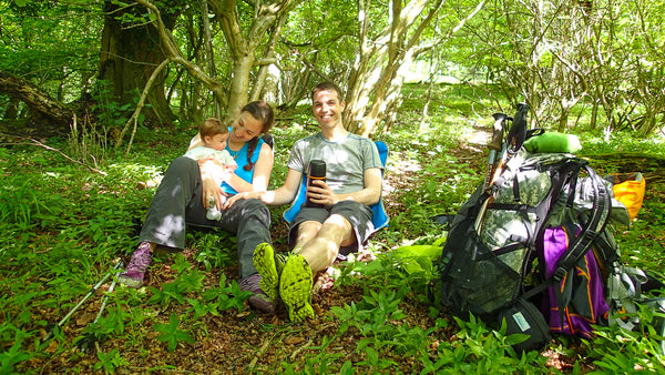 young smiling parents with a baby sit in the woods with packed backpacks next to them