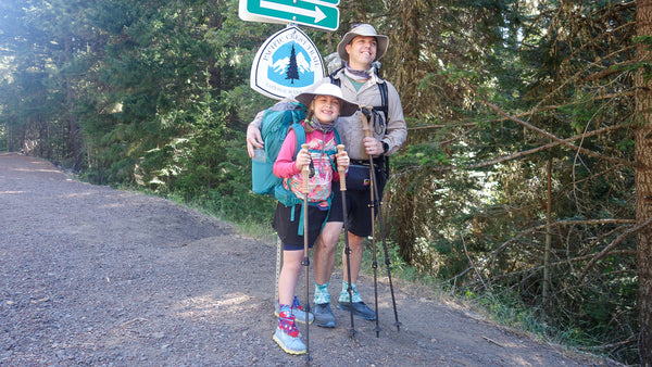 father and daughter stand in front of PCT sign with loaded packs on