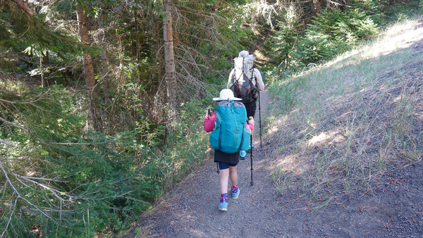 Father and Daughter walk away from the viewer on a trail with full backpacking packs on.