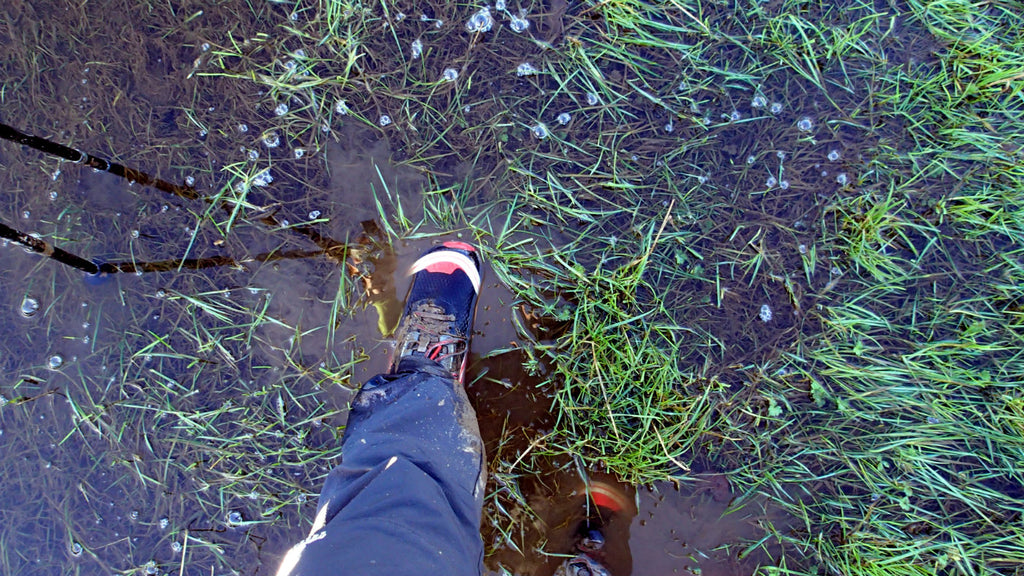 feet in running shoes in a large puddle