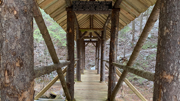 Looking out across a narrow wooden covered footbridge, with a wooden trail sign posted at the top beam, and a creek running underneath. appalachian trail, hiking, anxiety, women, woman, solo, female, backpacking, backpacker, hiker, bridge, creek, outdoors