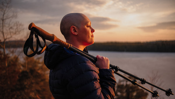 A woman with a shaved head holds a pair of CNOC trekking poles over her shoulder and looks out over the warm glow of a pink sunset and grey-blue body of water.  hiking, backpacking, solo, female, adventure, cancer, anxiety, women, female, hiker, outdoors, sunset
