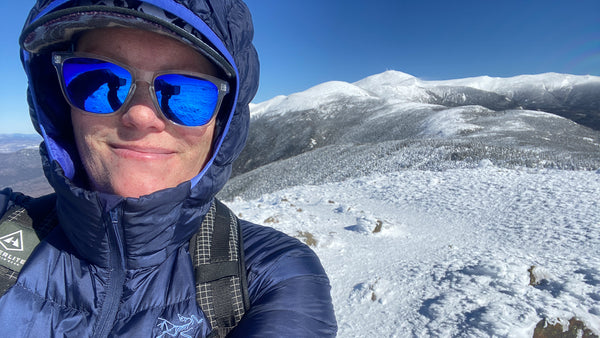 Rebecca smiles in a selfie on a snowy mountaintop wearing a blue down jacket and reflective sunglasses, with blue sky and mountains behind her. mountain, snow, hiking, backpacking, outdoors, solo, female, woman, selfie