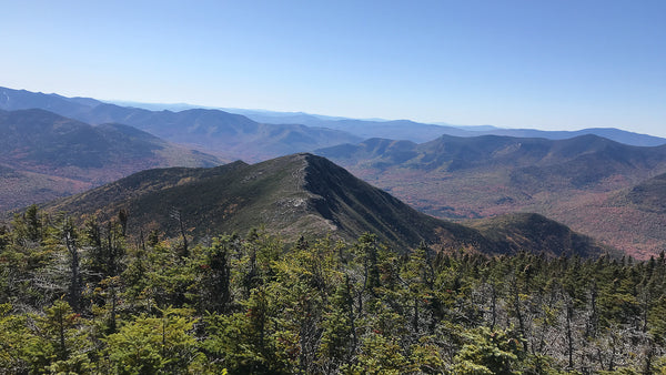 Taken from up high on a mountain ridge, a span of green and brown mountain ranges span into the distance, with evergreen trees up a slope in the foreground and a sunny, bright blue sky. backpacking, solo, outdoors, hiking, camping, female, women, woman, mountains, ridge, trails