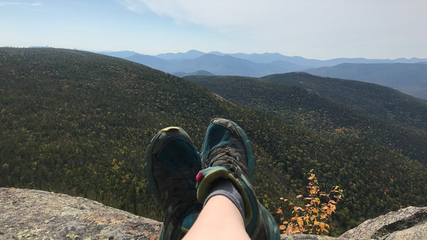 A pair of crossed feet in the foreground on granite, over a lookout with partial clouds and blue skies, rolling green hills and mountains. clouds, sky, mountain, solo, woman, female, hiking, backpacking, backpacker, cnoc outdoors, hiking boots, wilderness, outdoors