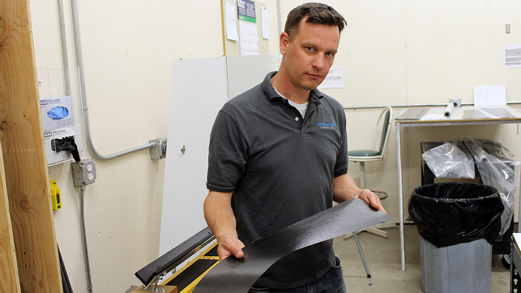 Goodwinds employee holding sheet of carbon fiber