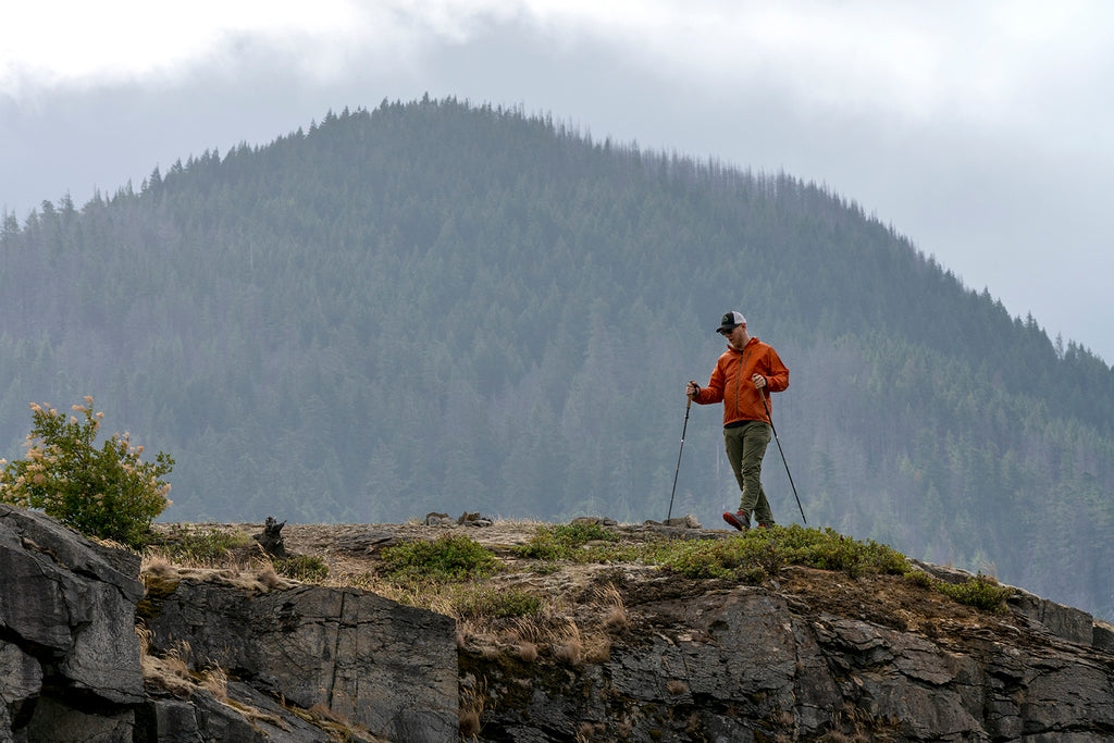Man walking with trekking poles on cliffside with mountain behind