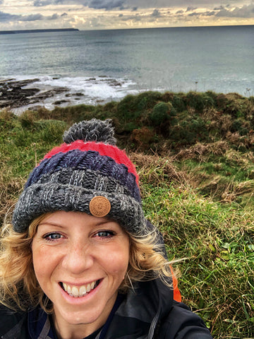 Gail smiling in a winter hat with the ocean in the background