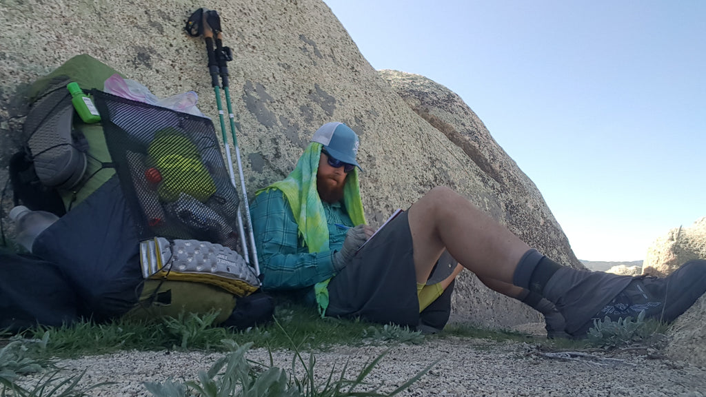 Brandon resting against a rock, pack and poles nearby