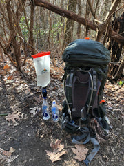A vecto water container next to a backpack in the woods