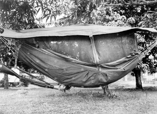 bw photo hammock with rifle hanging below