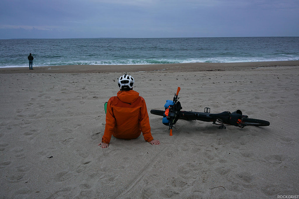 author sitting on beach next to bike