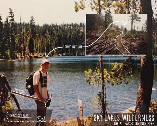 Young Man who is a professional trail worker stands in front of a lake holding a Pulaski.