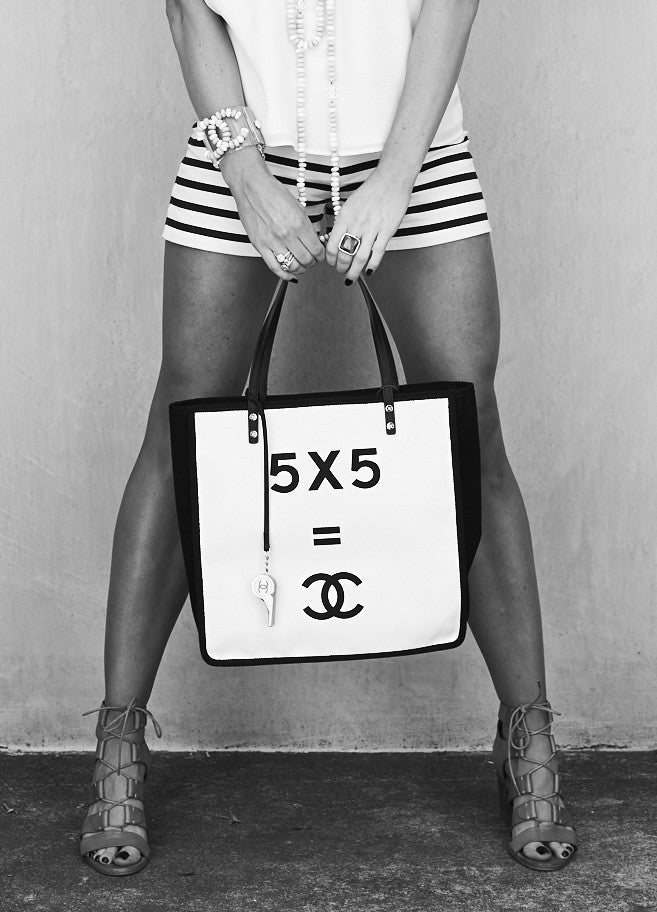 Woman holding a Chanel handbag wearing luxurious Chanel fashion accessories.