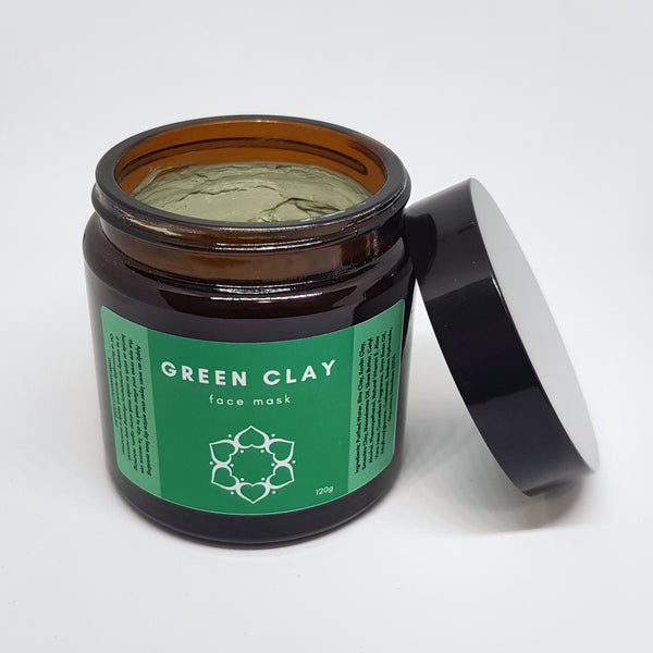 Product image of green clay face mask in an amber glass jar. It has a large green sticker on the front.
