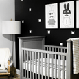 monochrome nursery designed in a superhero theme with white bat mask against the black wall