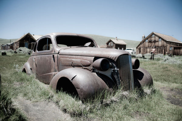 A photo of a old scrap car in a farm field. Photo is a free high resolution stock image to use any way you choose.