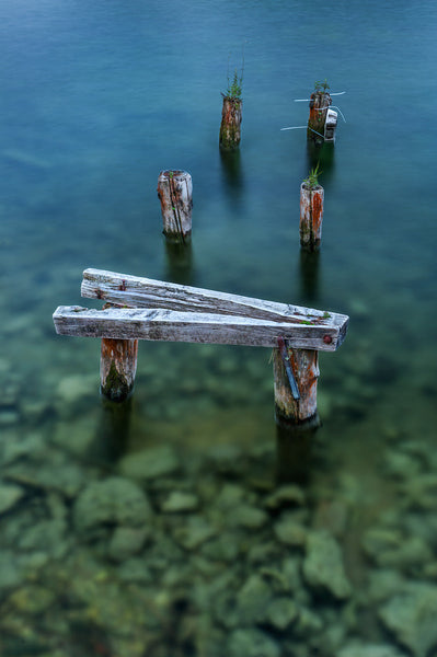 A photo of a broken-down, weathered pier in shallow Austrian waters. Photo is a free high resolution stock image to use any way you choose.