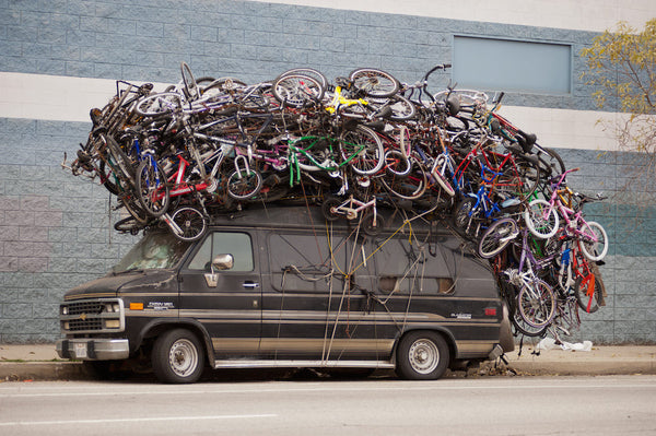 A photo of a Chevy Van with a ton of bicycles strapped to the roof. Photo is a free high resolution stock image to use any way you choose.
