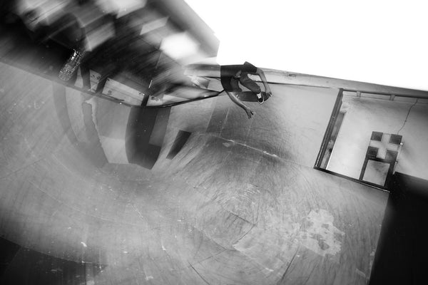 A photo of a skateboarder carving a vert section in a bowl. Shot in black and white. Photo is a free high resolution stock image to use any way you choose.