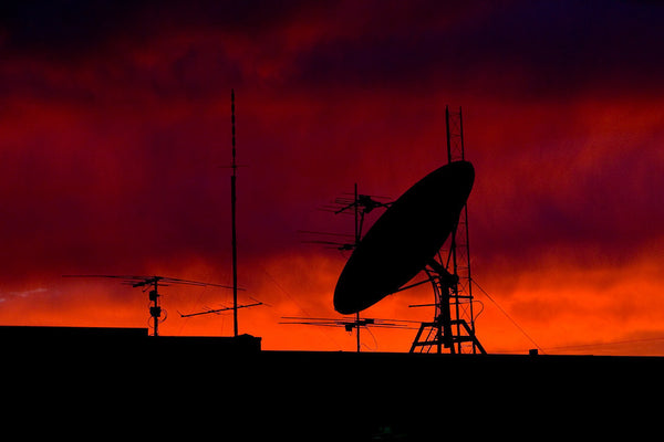 A photo of a satellite at dusk with a red sky. Photo is a free high resolution stock image to use any way you choose.