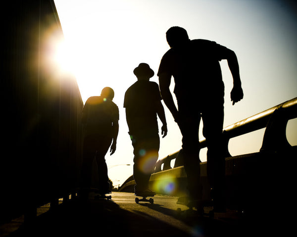 A photo of a group of skateboarders pushing into the sun. Photo is a free high resolution stock image to use any way you choose.