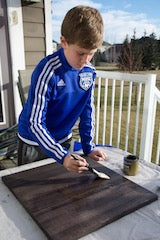 Quinn applying the second coat of stain.