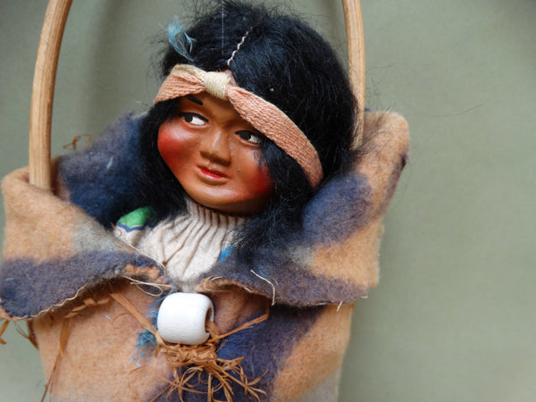 Skookum papoose doll in cradle, looking right