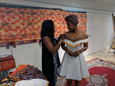 Model being fitted for our Ambazinia off-shoulder dress