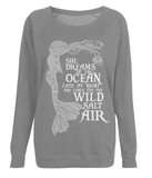 "EP66 Organic Combed Cotton Unisex Dark Heather Raglan Sweatshirt contains the emotive and mermaid inspired quote ""She Dreams of the Ocean late at night and Longs for the Wild Salt Air"""