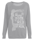 "EP66 Organic Combed Cotton Unisex Light Heather Raglan Sweatshirt contains the emotive and mermaid inspired quote ""She Dreams of the Ocean late at night and Longs for the Wild Salt Air"""