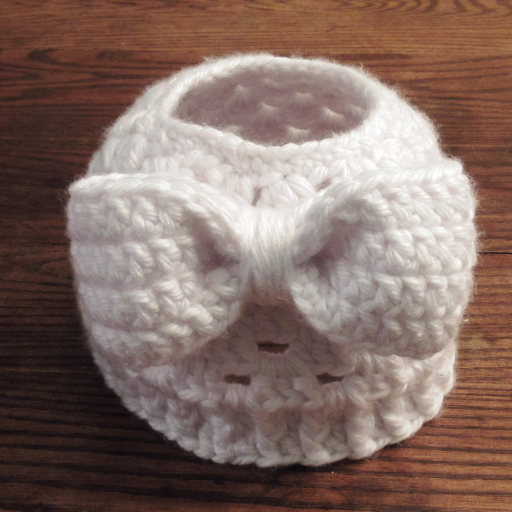 white hand crocheted messy bun hat with attached bow