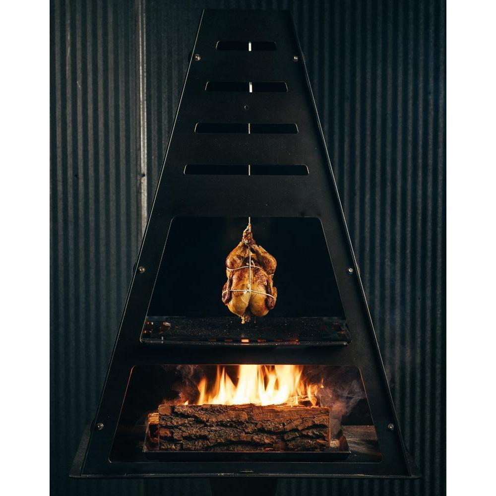 Roasted chicken hanging from Pyro Tower cooking over wood fire