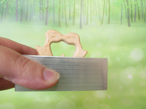 Mass produced wooden penguin teething toy made in Asia being put through the mandatory rattle testing device and passing the first test for teething toys