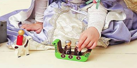 Girl playing with MDH Toys Dragon Viking Castle. Handmade wooden toy made in Canada by M.D. Handfield Designs Inc.