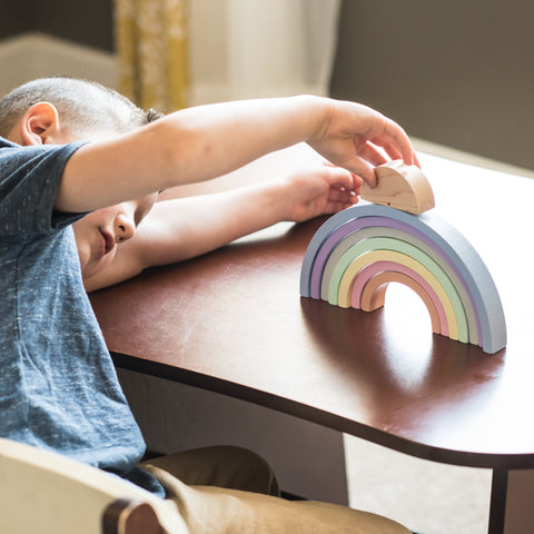 Boy playing with MDH Toys Wooden Rainbow. Photo by Lana Palmer Photography