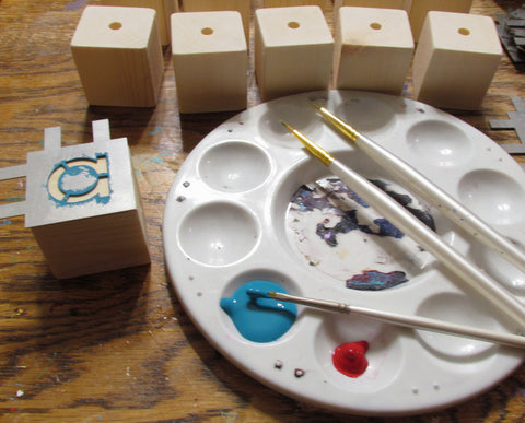 Painting the letters onto solid wood blocks for MDH Toys Montessori Style Reading Spinners by M.D. Handfield Designs. Handmade wooden educational toys made in Canada