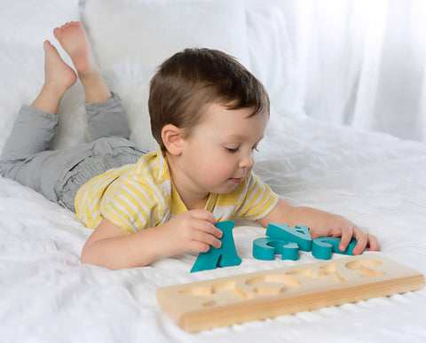 Boy playing with MDH Toys solid wood custom name puzzle made in Canada by M.D. Handfield Designs Inc. Solid wood toy photograph by Tannielle Williamson Photography. (c)2018 all rights reserved.