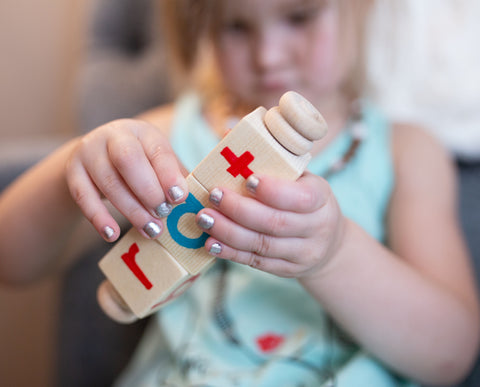 Girl playing with mixed vowel reading spinner. Preschool wooden educational toy made in Canada. Photo by katlin shuherk photography