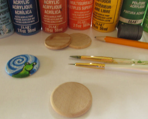 Materials and supplies needed to paint a wooden magnet to look like a snail